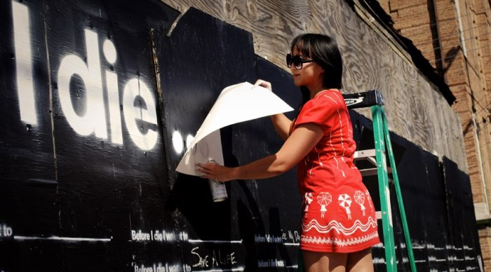 Candy preparing her first wall with the stencil that she later created as part of the 'Before I Die...' toolkit